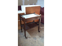 old dark wood tea trolley with drawer and glass insert at the top