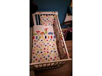 Baby cot with new mattress and bedding.