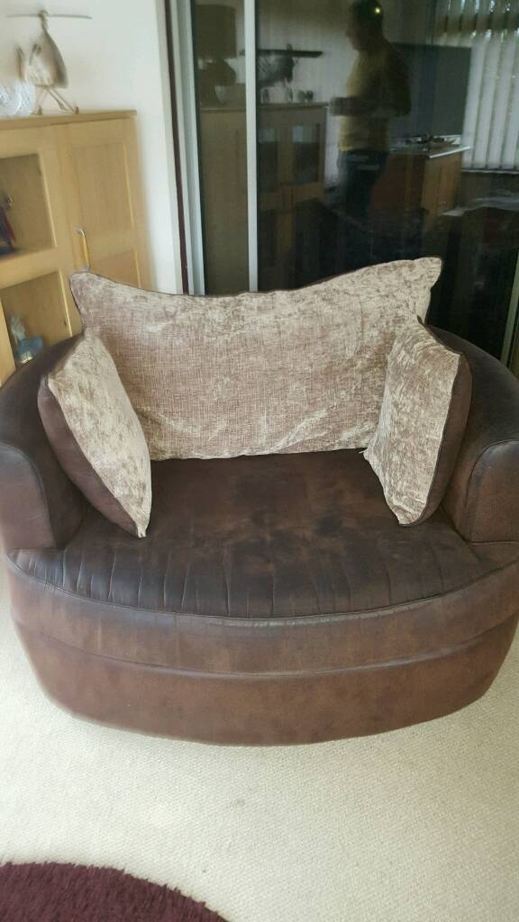 Brown swivel cuddle chair.