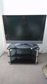 """32 """" Hitachi LCD TV and black and silver glass stand for sale."""