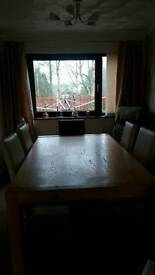 Oak table and chairs sits eight