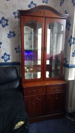 a beautiful reproduction glazed cabinet above a cupboard