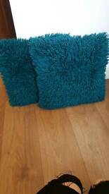 Two teal shaggy cushions