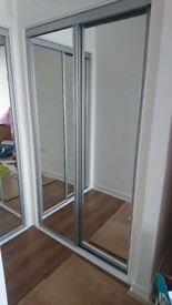 Two sliding plain mirrored wardrobe doors complete with top and bottom tracks