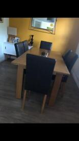Dining table and six chocolate brown faux-leather dining chairs