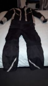 motorcycle suit 2 pairs of boots size 7 and a pair of gloves