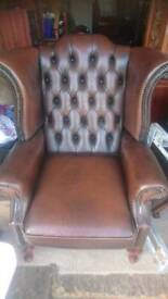 An Antique brown leather Chesterfield wing chair in good condition throughout