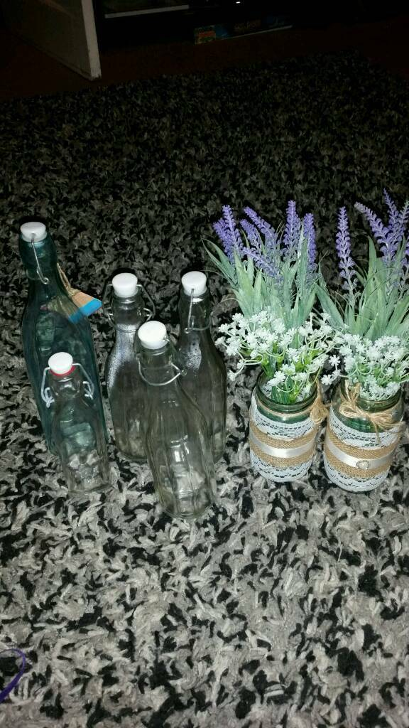 5 glass bottles and vase with flowers in