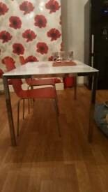 Ikea table with four red chairs