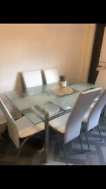 Glass dining table and white leather chairs