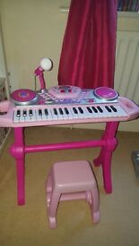 Pink piano with stool and microphone