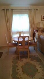 A very attractive hand painted in cream wooden pedistal round dining table and matching four chairs.