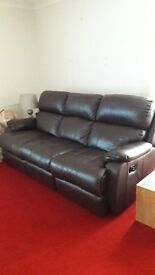 Two leather brown leather sofas with recliners.