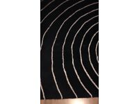 black with white swirly pattern 120cm x 180cm rug £10 (NG5 area)