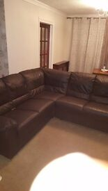 A fairly used dark brown 5/6 seater corner sofa.