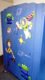 Large antique style double wardrobe painted in kids theme.