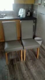 Pair of grey faux leather chairs with light oak legs