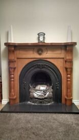 Wooden fireplace, grate and cast iron surround