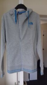 A brand new ladies' North Face hooded and zipped to the bottom grey top, size L