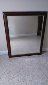 Large, dark wood mirror with carved and gilt trim