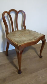 Antique chair with ornate curved wooden back rest