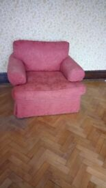 Large armchair in terracotta coloured upholstery.