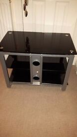 Black glass TV stand. Only selling as have put tv on the wall.