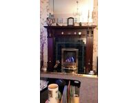 Wooden fire surround with tiled inside and tiled hearth, brass fender and fire trim