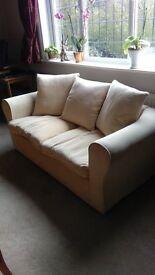 Two seater cream fabric sofa.