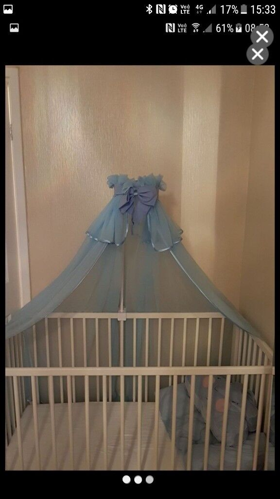white cot including blue drape and mattress