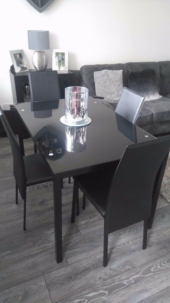 Black glass dining table and four leather chairs