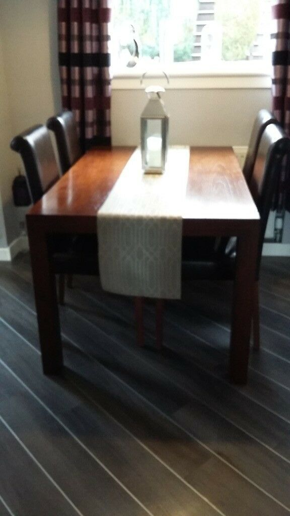 Dark wood dining table with 4 brown leather chairs
