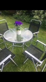 Brand new patio / garden table and chairs bought for £85. Glass table top and 4 fold up chairs