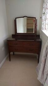 Antique 3 draw dressing table with protective glass top and wheels.