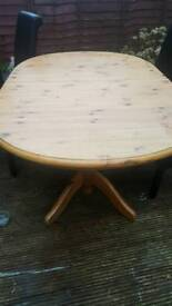 Extending wooden table and cushion chairs