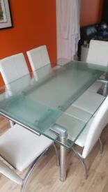 Glass dining table and 6 white faux leather chairs