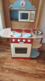 Wooden solid built kitchen with sink. Microwave and oven.