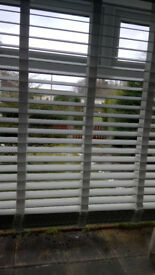 Two solid white wooden blinds