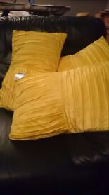 Brand new, labels still attached. 3 gold colored silk like feather filled cushions