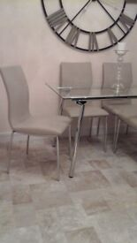 Modern glass and chrome dining table and 4 cream streamlined chairs