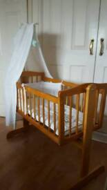 Wooden crib with bedding and drape rod