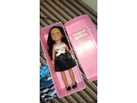 Designa Friend doll in original box, comes with various outfits, wardrobe and suitcase / passport.
