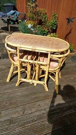 compact cane table and 2 chairs with cusions