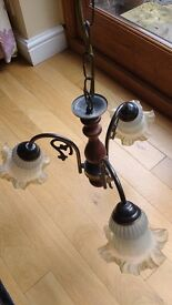 A pair of 3 arm traditional ceiling lights with frosted glass shades in wood and brass finish