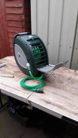 Wall mounted hose reel with bracket to fix to wall or fence this item is new.