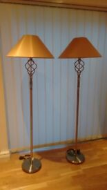 Two matching polished brushed finished standard lamps.
