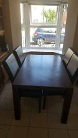 Solid wood table with 4 leather chairs.