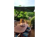 8 seater teak table and chairs with cushions,lazy susan and wind up parasol and metal base.