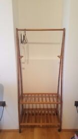 Wooden clothes rail with lower shelves for storage