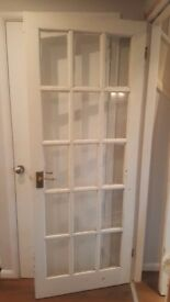 Painted solid wood and glass door. Requires a little TLC but no damage.
